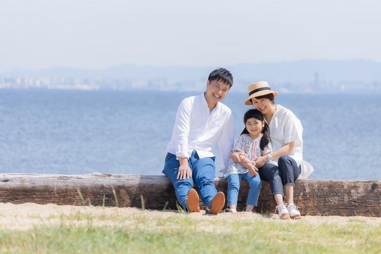 海沿いで家族写真を撮影するハルさん